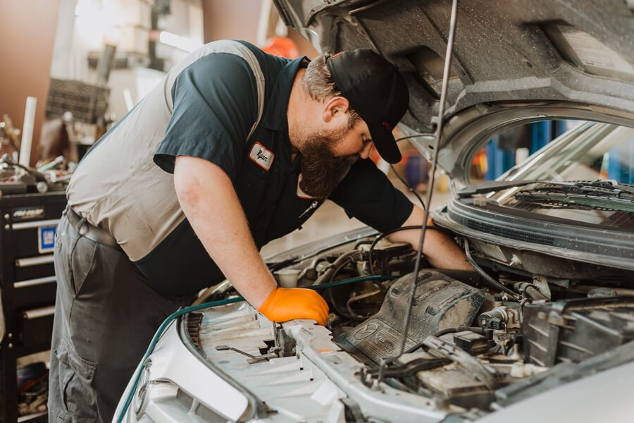 auto technician working on A/C system of a vehicle