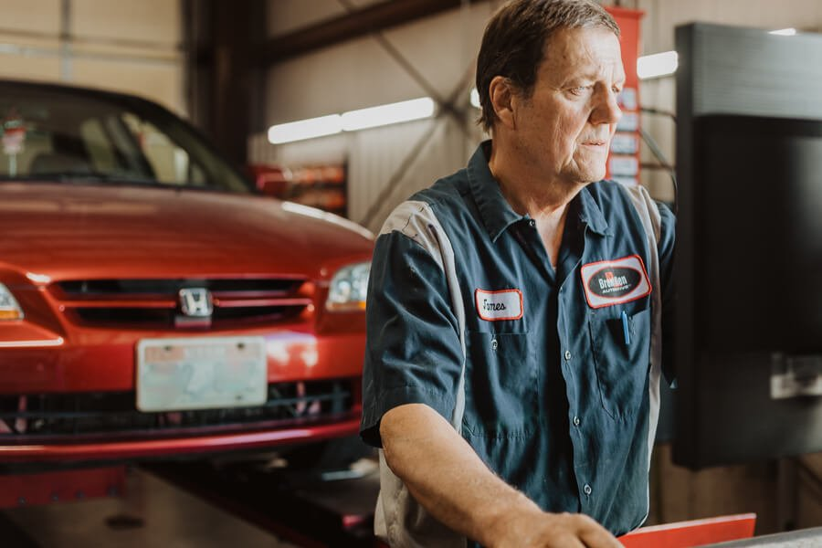 auto mechanic providing wheel alignment service for a vehicle in North Logan, Utah